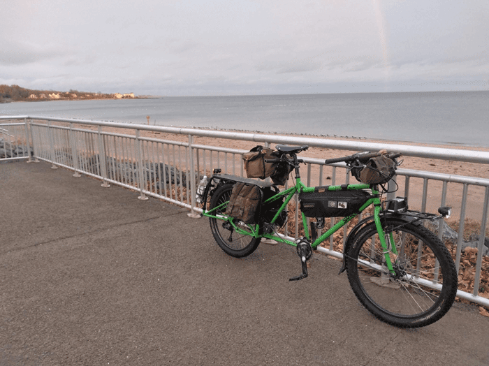 Left side view of a green Surly Big Dummy bike with fenders loaded with gear bags, leaning on guardrail above a beach