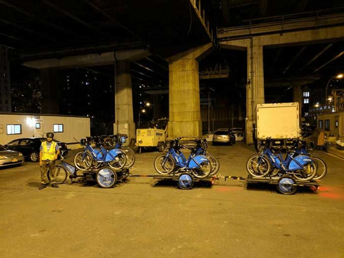 Person standing under a bridge at night in front of a three wheeled bike with two trailers loaded with bikes connected