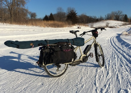 Surly Big Easy bike, tan, with rear saddle and ski bag shown on top of a snow covered cross country ski trail in nature