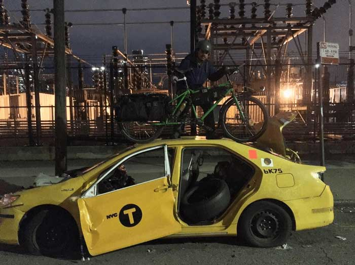 Cyclist with a green Big Dummy bike on the roof of a yellow broke down NYC taxi at night in front of an electric station