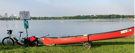 Left side view of a tan Surly Big Easy bike with a trailer carrying a red canoe attached, in the grass beside a lake