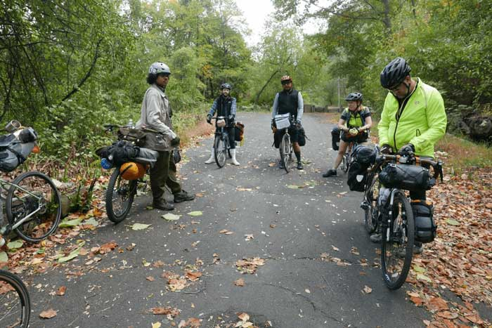 Four cyclists standing with their bikes loaded with gear on a paved trail in the woods