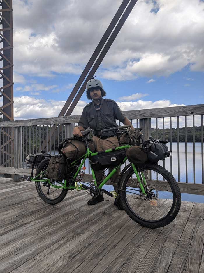 Cyclist standing on a wood bridge over a river with a green Surly Big Dummy bike with blue sky and clouds in the sky