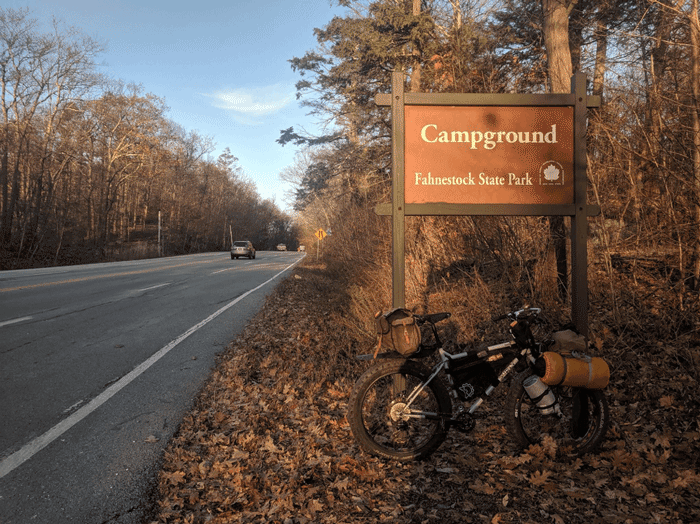 Right side view of a white Surly Pugsley fat bike leaning of a Fahnestock State campground sign beside paved roadway