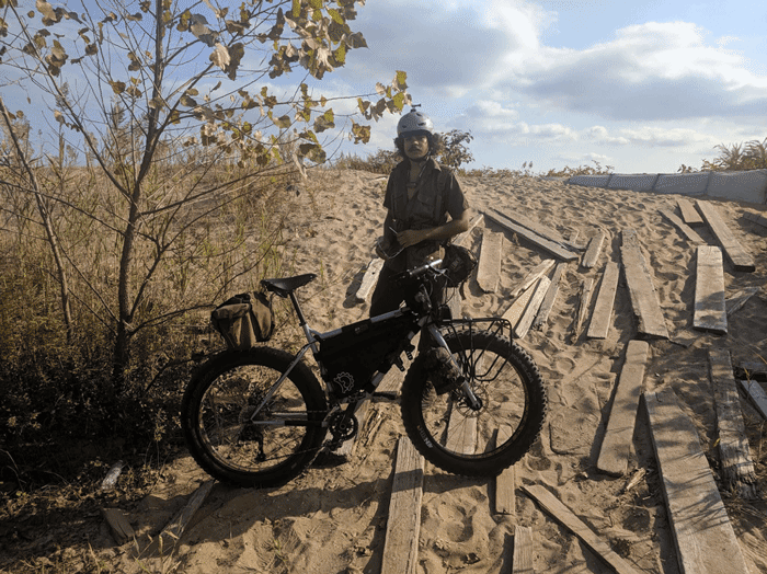 Right profile of a white Surly Pugsley fat bike loaded with gear and cyclist standing behind on a sandy plot with boards
