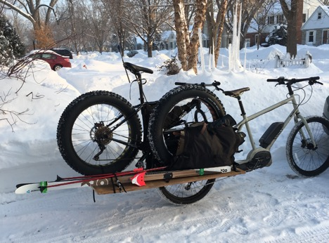 Right side view of a tan Surly Big Easy bike and trailer hauling a fat bike and skis on a snow in a neighborhood