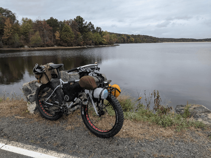 Right profile of a white Surly Pugsley fat bike loaded with gear on the shoulder of a paved road on the edge of a lake