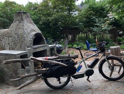 Right side view, Surly Big Easy bike,tan, with saddle bags loaded with firewood near outdoor wood stove on a patio
