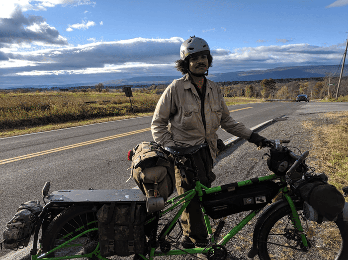 Right profile of a green Surly BIg Dummy bike on the shoulder of a remote paved highway with cyclist standing behind