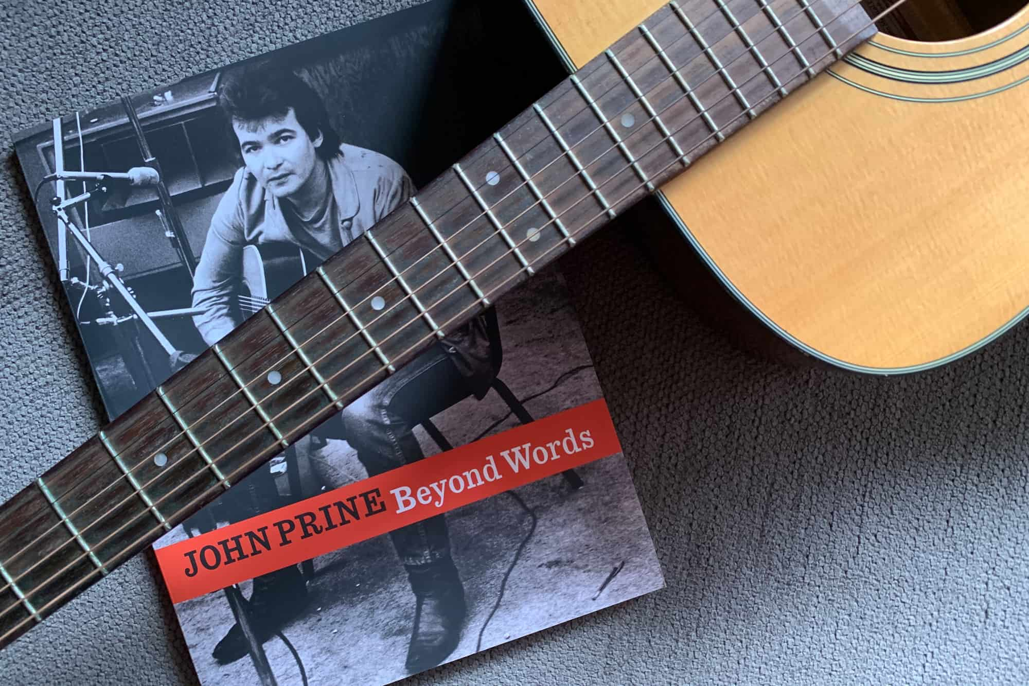 Portrait of John Prine book Beyond Words lying on short gray carpet with the neck of an acoustic guitar laying across