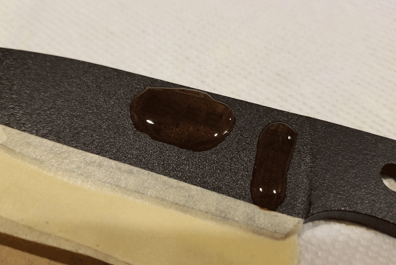 Portion of black powder coated knife blade with drops of acid on it and  taped to a white mat working surface