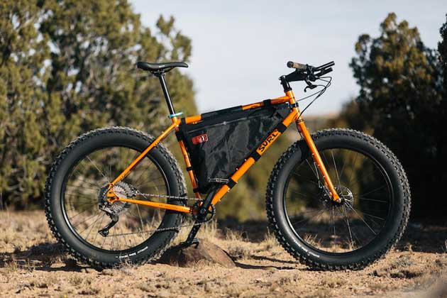 Right side view of an Surly Pugsley fat bike, orange, with inner frame pack, on sandy and rocks with trees in the background