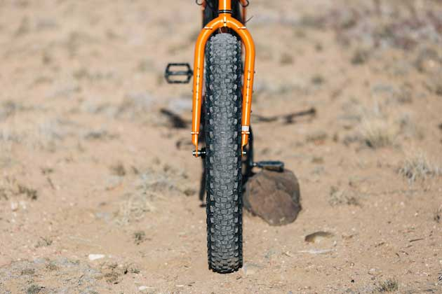 Front, head tube down view of an orange Surly Pugsley fat bike, parked on desert sand