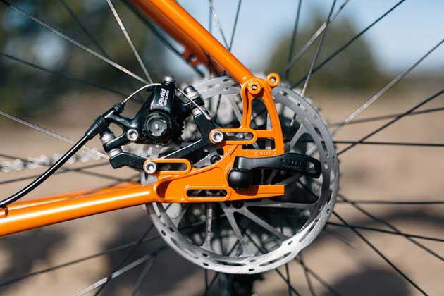 Zoomed in left side view of the rear axle plate, brake disc and brake caliper of a Surly Pugsley fat bike, orange