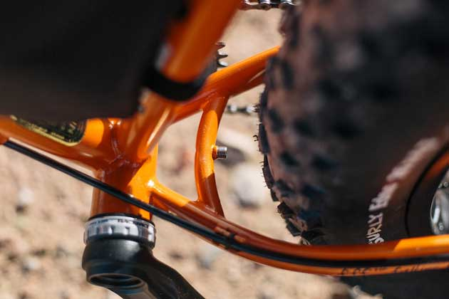 Zoomed in downward partial view of the left crank arm, seat tube, chain stay on a Surly Pugsley fat bike, orange