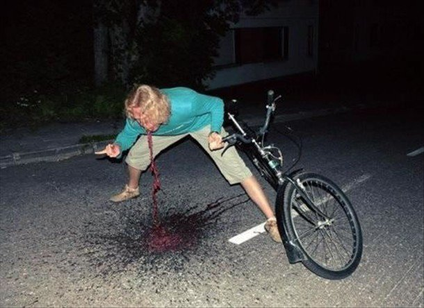 Front view of a person leaning over and throwing up, with a bike leaning on them, on a street at night