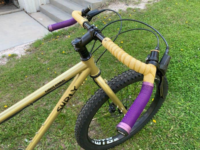 Surly Karate Monkey with Corner Bar installed with purple mountain grips installed in the drops and gold bar tape on the top