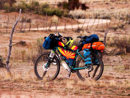 Left side view of a Surly Troll bike, loaded with gear, standing in desert grass, with a road in the background