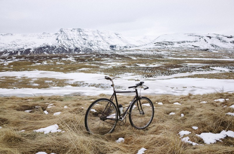 Rear, right side view of a black Surly bike, in a field of brown, flowy grass and snow, facing snowy mountains