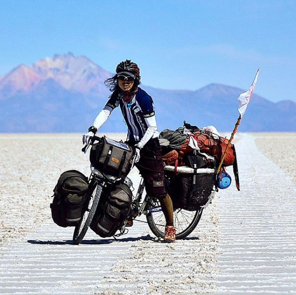 Cyclist facing toward camera while standing on a sandy road with a bike loaded with gear and mountains behind