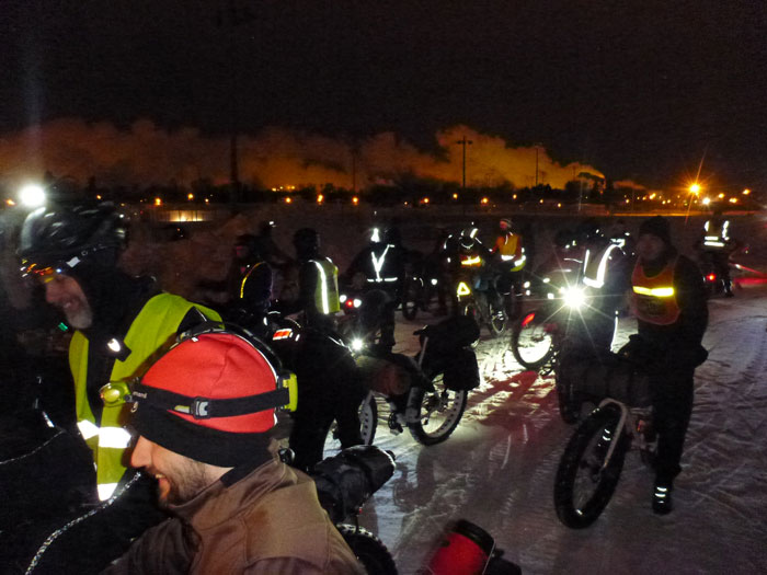A group of winter cyclist and their bikes, standing on a snow covered road at night