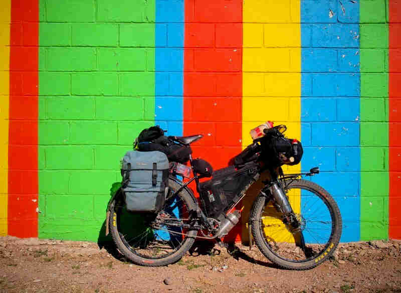 Right side view of a Surly Troll bike, loaded with gear, leaning against a color strip cinder block wall