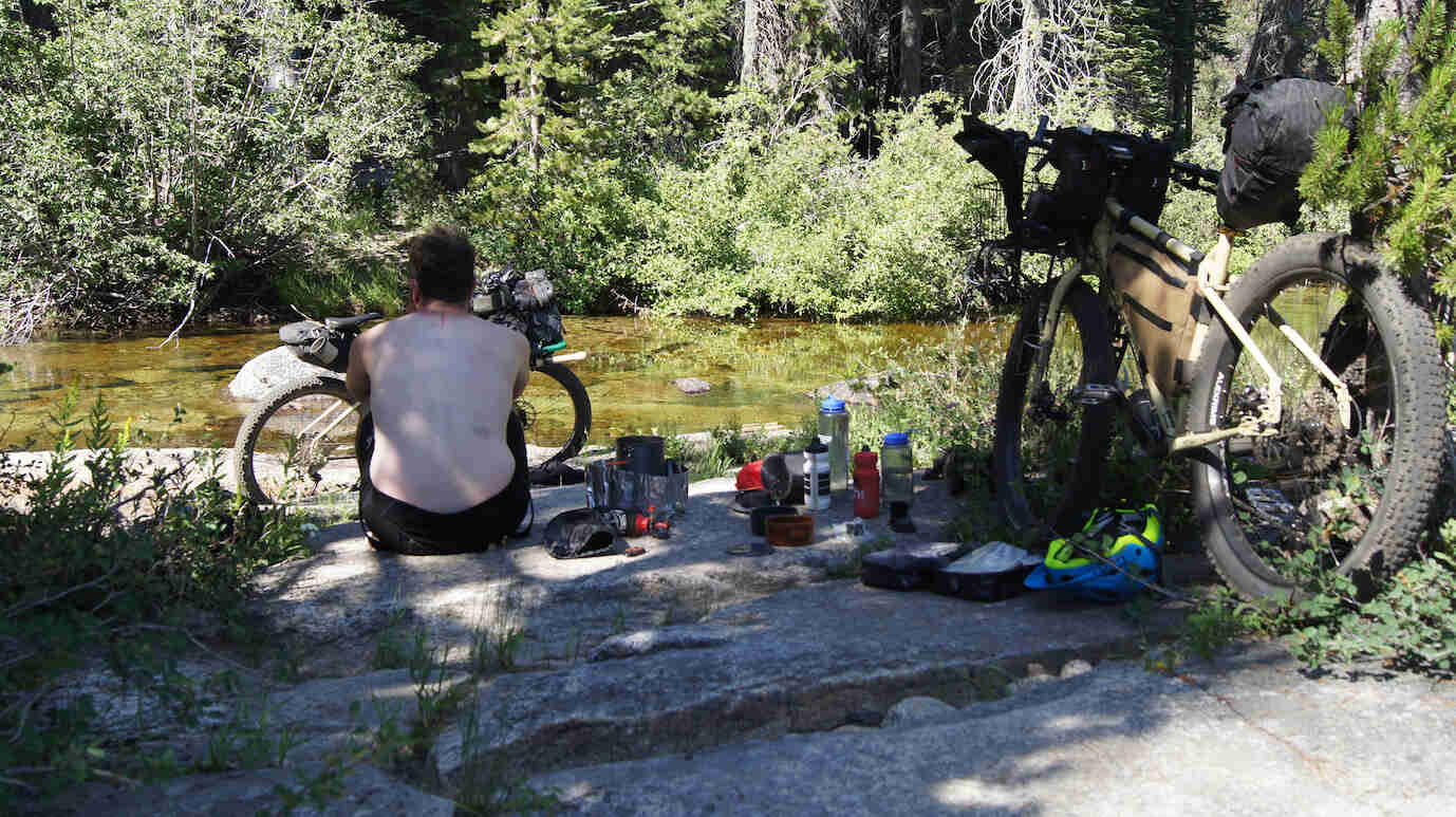 Rear view of a person sitting on a flat rock behind a fat bike,facing across a stream, with a Surly fat behind them