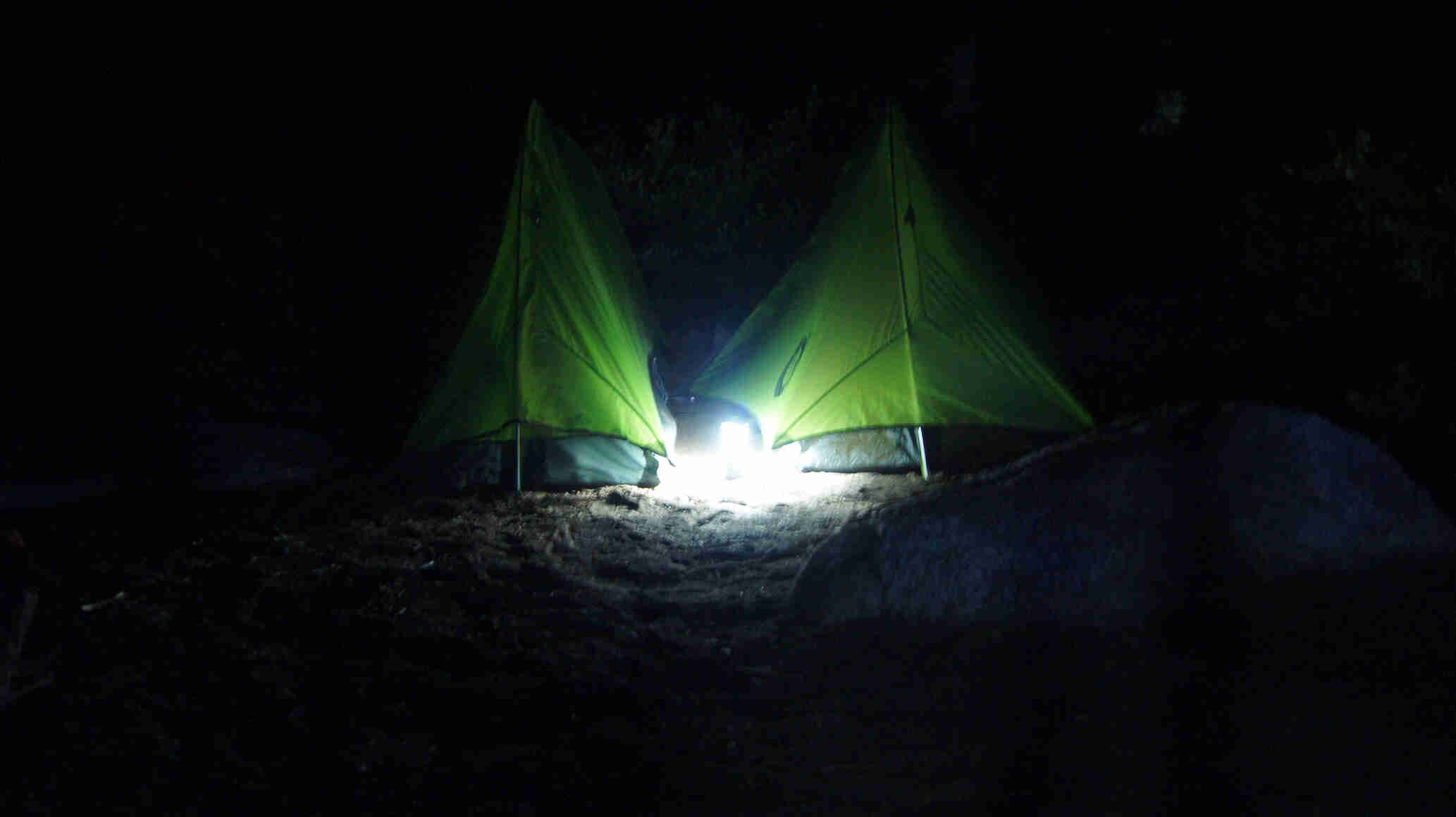 Two tents, next to each other, at night, with a light on the ground between them