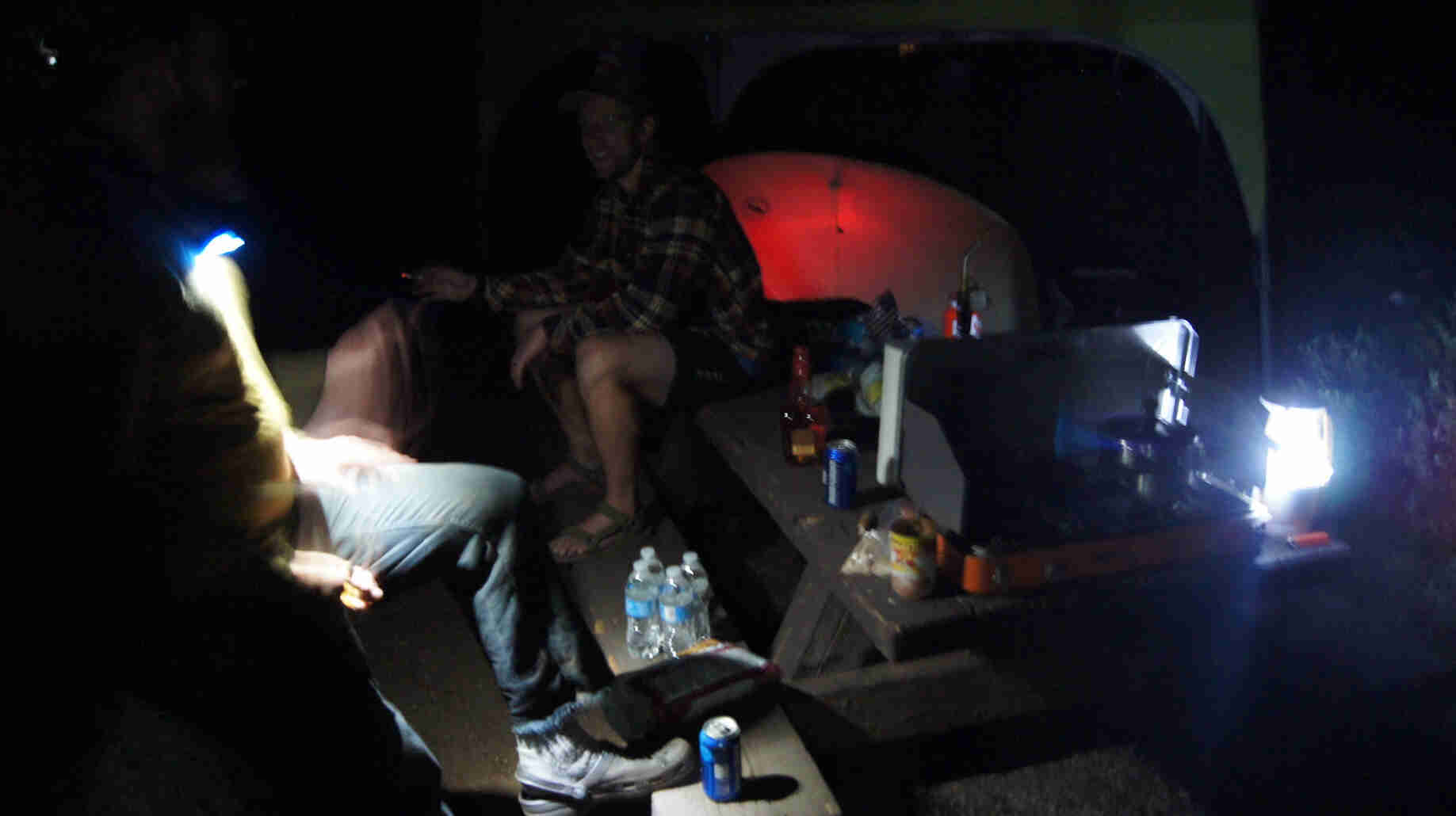 2 people sitting on a picnic table, at a campsite at night, with a tent in the bacground