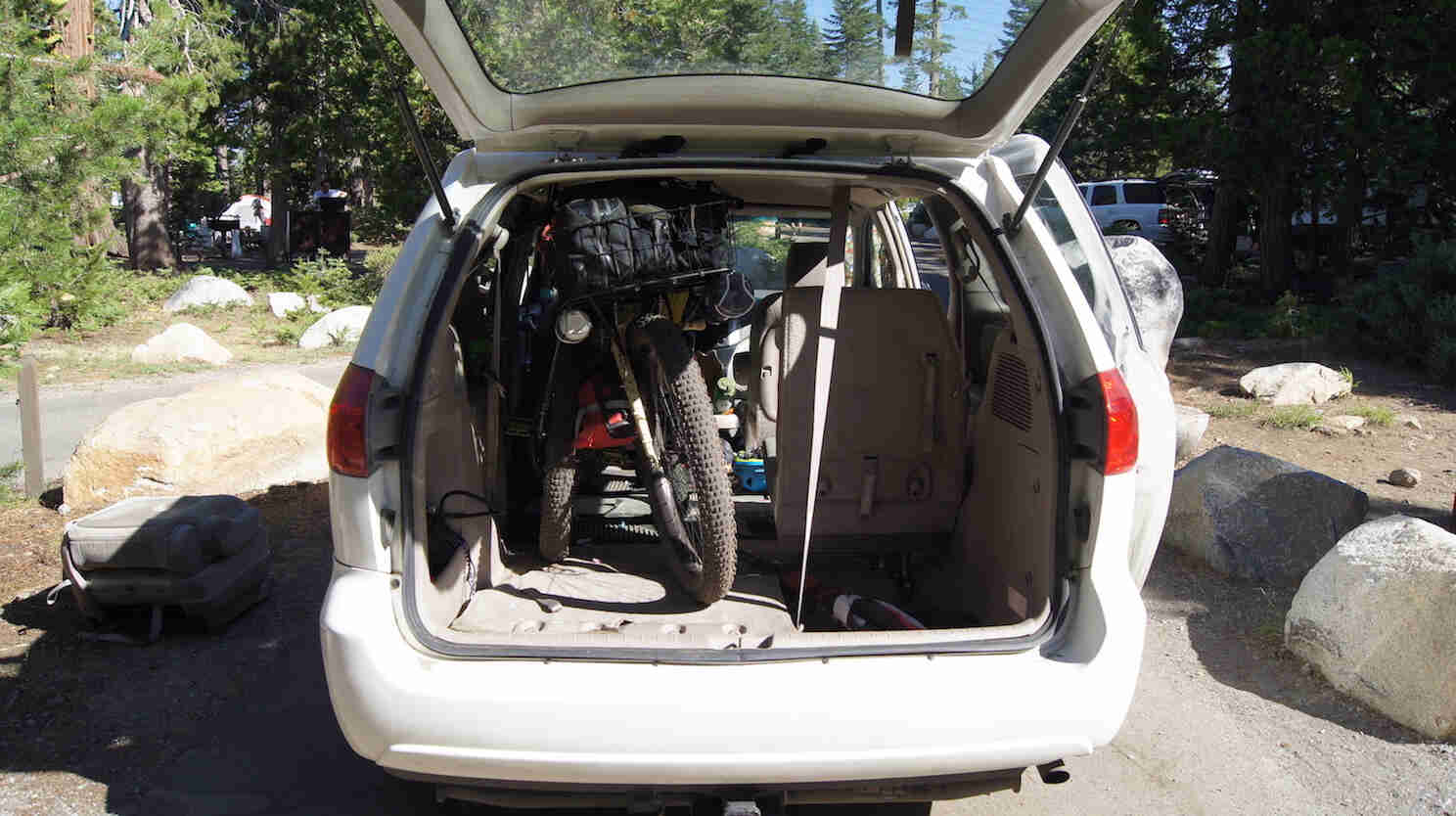 Rear view of a minivan with the back door open, with bike loaded in back