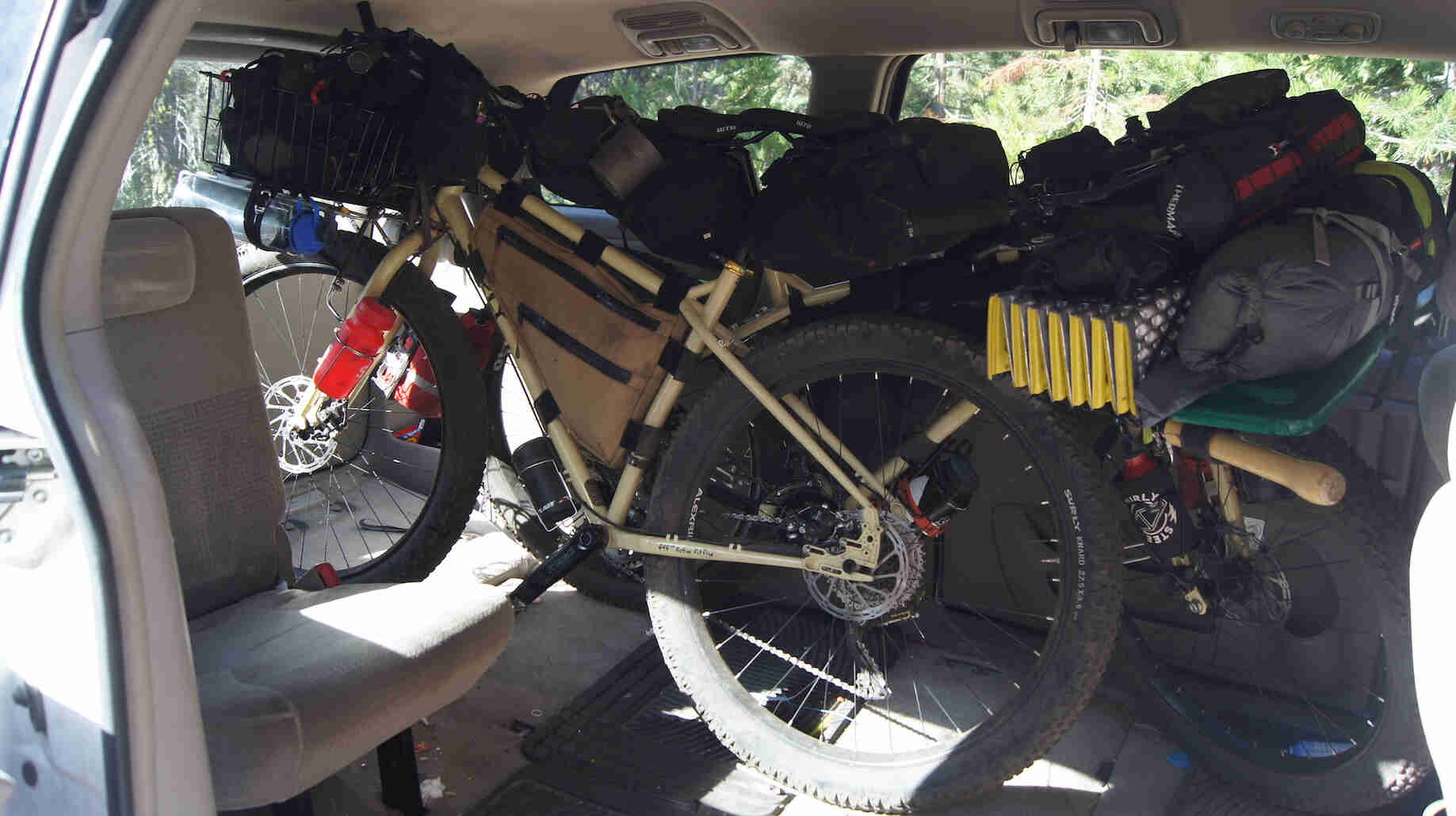 Left side view of a Surly bike, inside of a minivan with camping gear