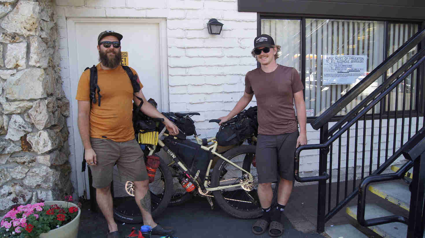 Front view of two cyclists standing with Surly fat bikes, in front of a motel room
