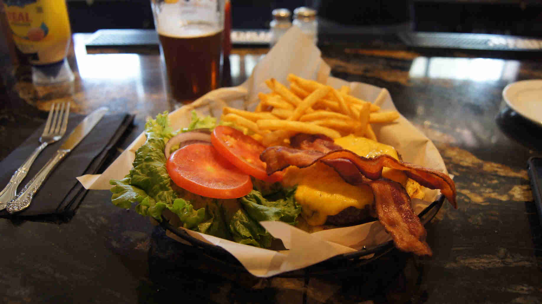 A food basket, with burger and fries, on a bar top