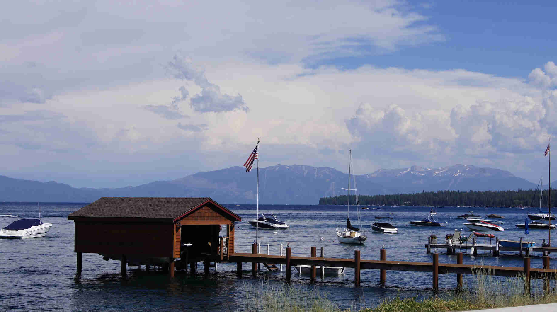 A dock with a boat house at the end, on a lake with boats, and mountains in the background
