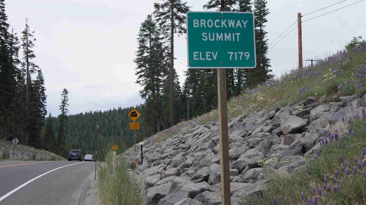 Sign showing Brockway Summit-Elev 7179, on the side of a paved road, with mountains and trees in the background