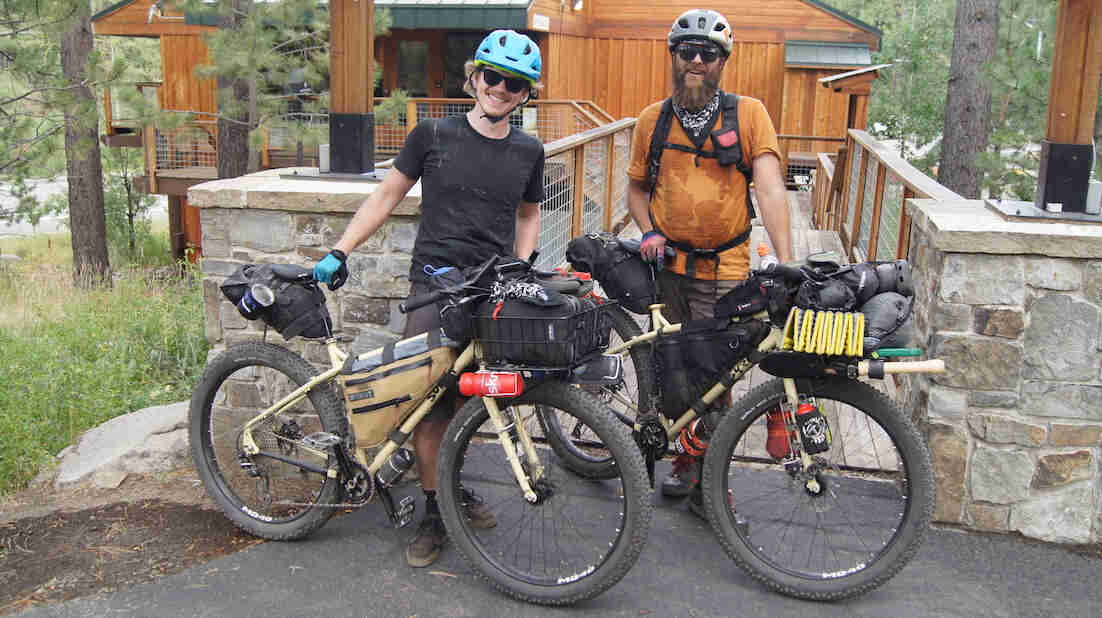Front view of two cyclists standing with their Surly bikes, with a wood sided building in the background