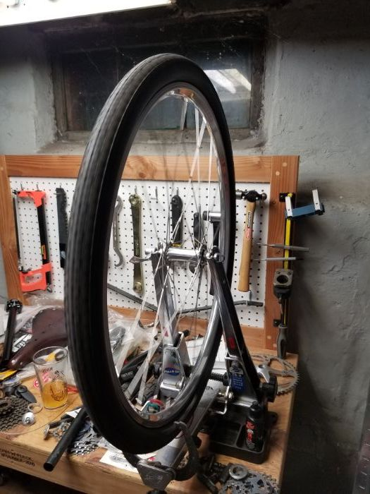 Assembled bike wheel with tire mounted to a rim truing device on a workbench with pegboard with tools and bike parts