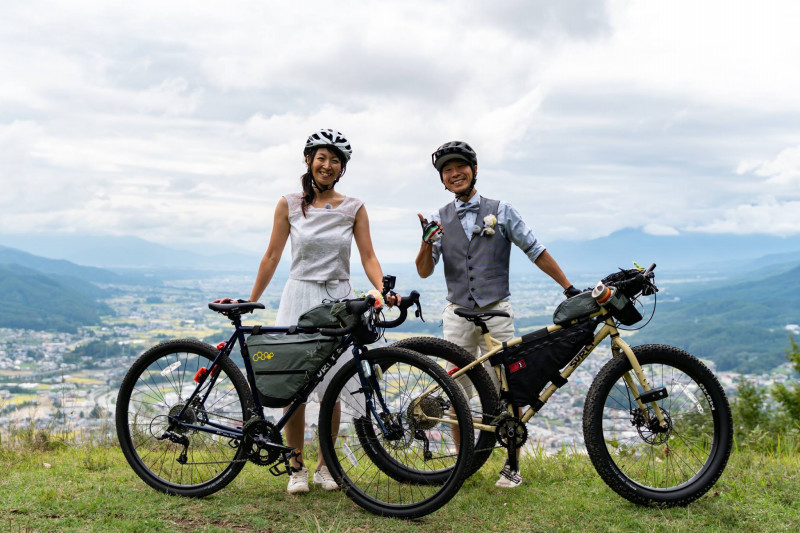 Two cyclists stand with their bikes loaded with gear dressed in wedding attire at an overlook of a mountain city