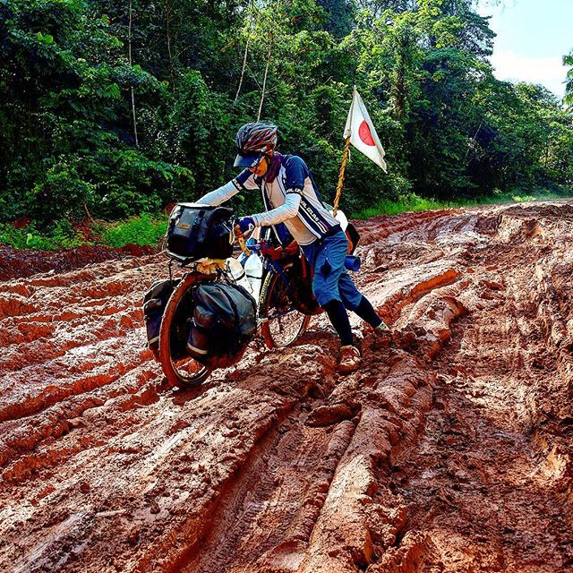Cyclist pushing bike loaded with gear and Japan flag on back, through a deep, red mud road and forest in the background