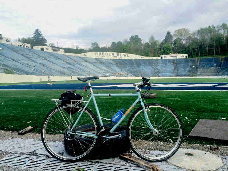 Right side view of a mint Surly Cross Check bike, parked inside an empty football stadium