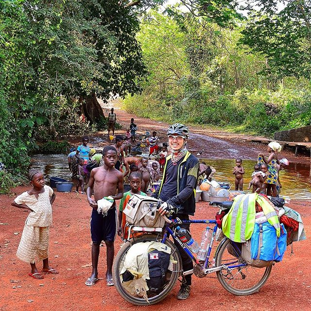 Cyclist standing on red dirt with a blue Surly bike with gear is surrounded by children in front of a forest river