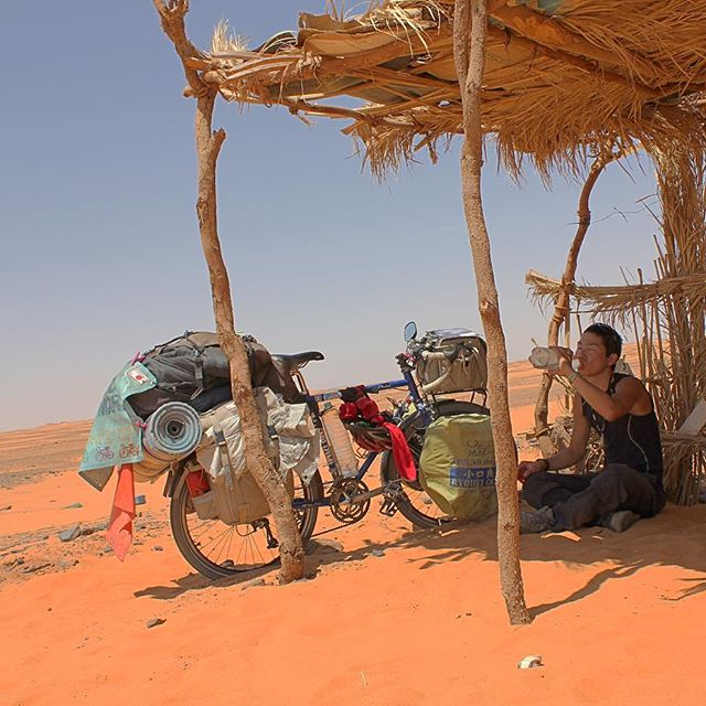 Cyclist sitting on red sand drinking water under a grass and stick canopy next to a blue Surly bike loaded with gear