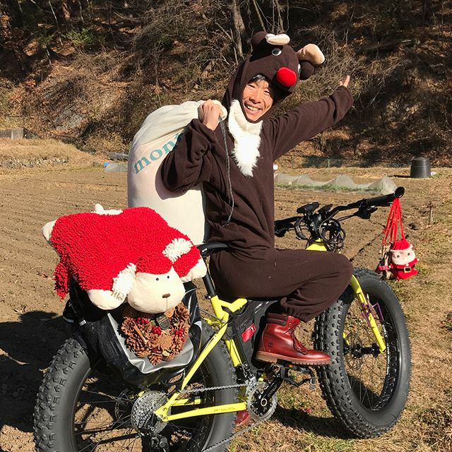 Cyclist  wearing a reindeer costume seated on Surly fat bike,lime, looks back while pointing at a hill