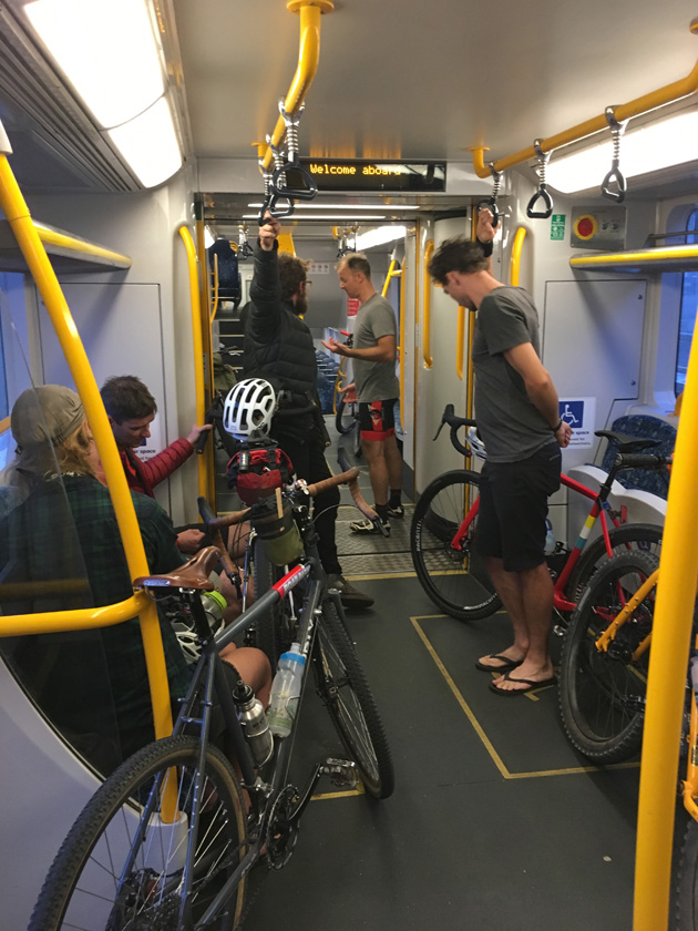 Cyclists standing and sitting inside of city commuter rail car
