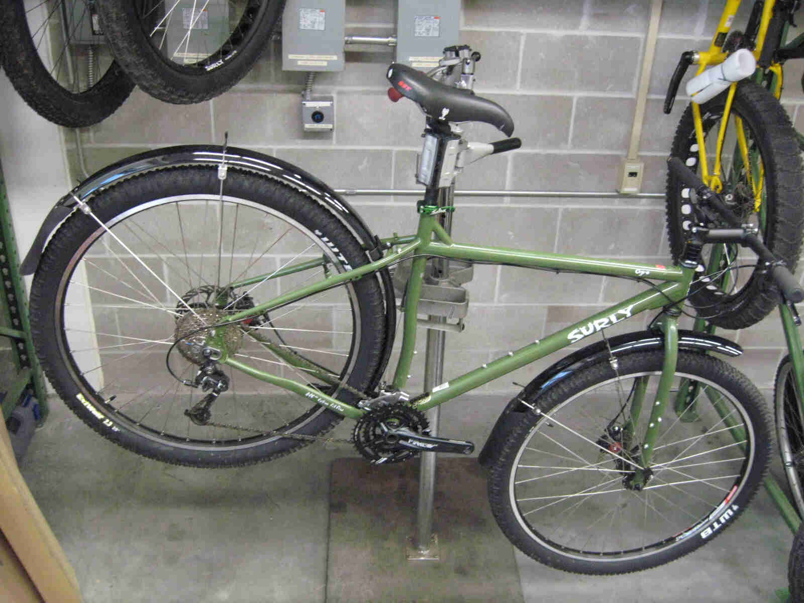 Right side view of a green Surly Ogre bike with fenders, mounted to a bike repair stand, inside a workshop room
