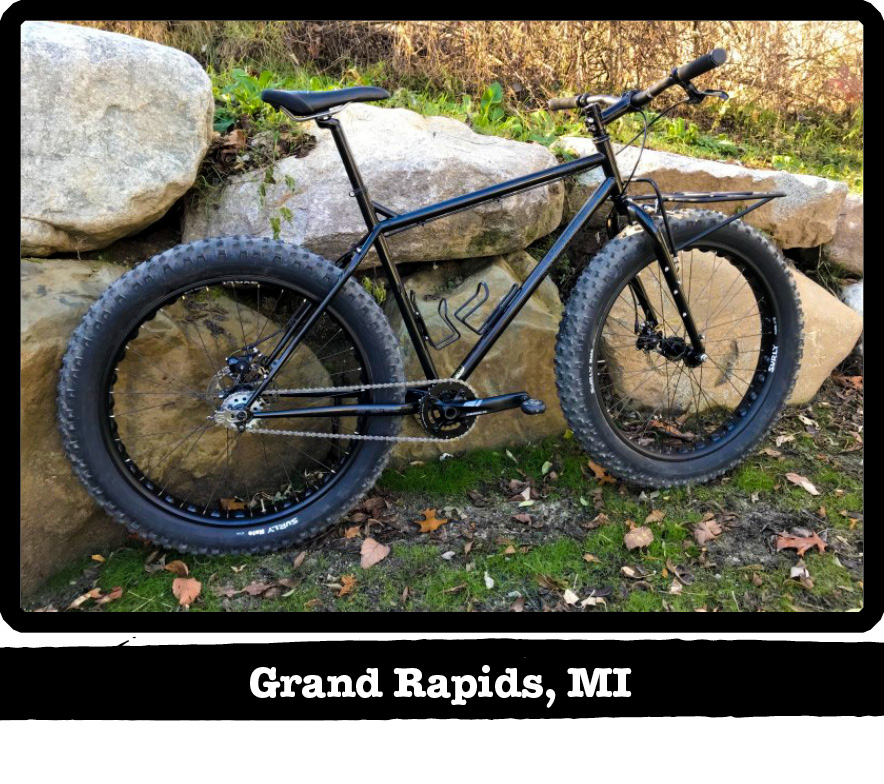 Right side view of a Surly fat bike, black, leaning on a boulder wall amd brush above-Grand Rapid, MI banner below image