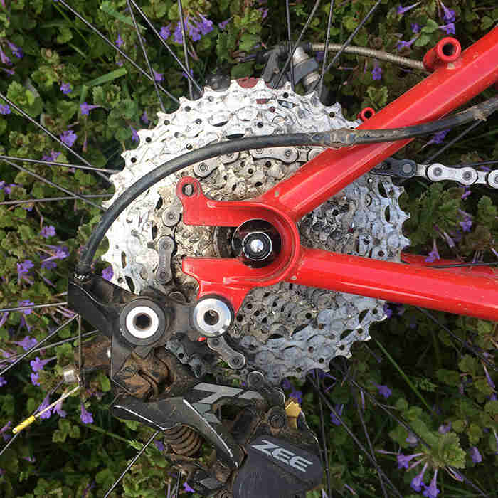 Close up view of the rear drop outs, cassette and derailleur of a Surly Krampus bike, red