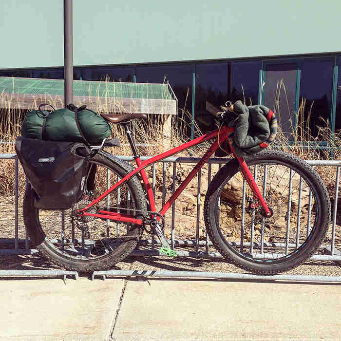 Right view of a Surly Krampus bike, red, loaded with gear, with a bike rack and building in the background