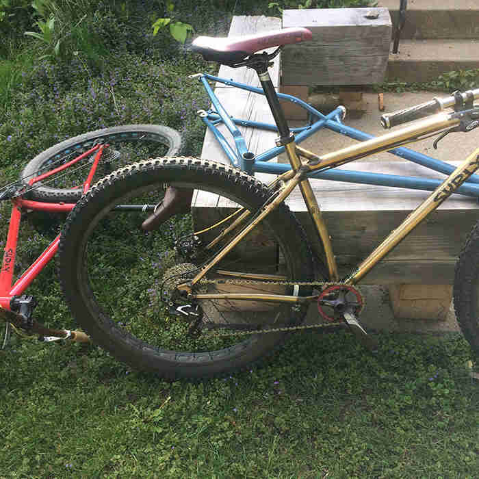 Two Surly Krampus bikes and one frame, on the grass next to a wood beam porch deck
