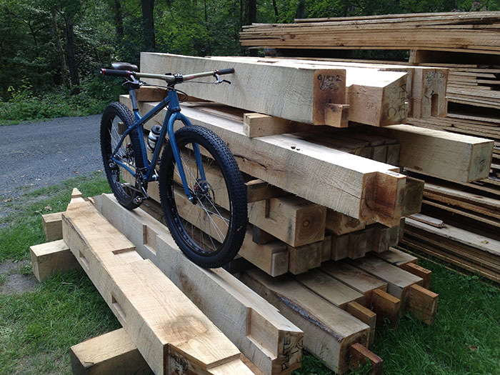 Front Right view of a Surly Krampus bike, blue, on a stack of square timbers, with a road and trees in the background
